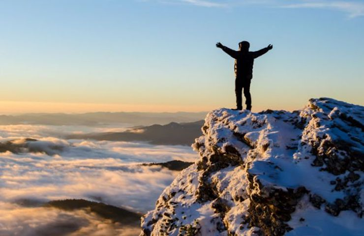 person-celebrating-reaching-top-of-mountain